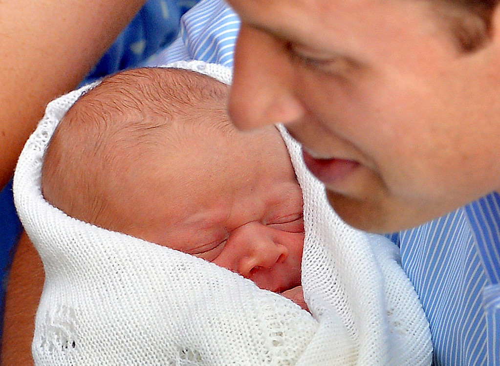 . Britain\'s Prince William holds his baby son outside the Lindo Wing of St Mary\'s Hospital before leaving with Catherine, Duchess of Cambridge, in central London July 23, 2013.   REUTERS/John Stillwell/POOL