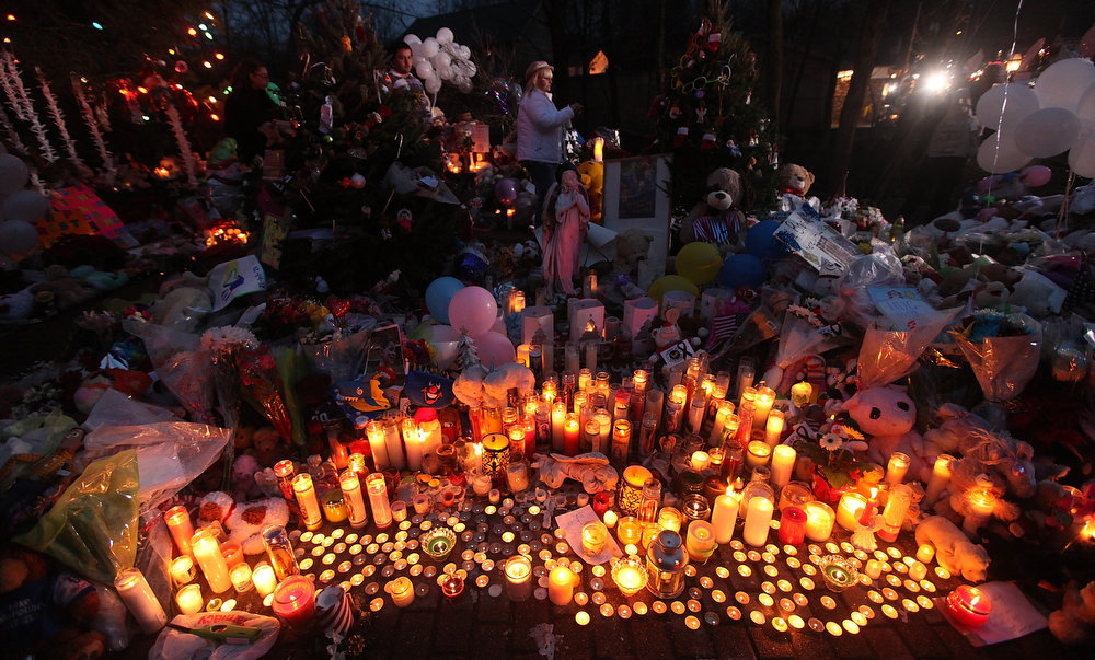 . Candles are lit among mementos at a memorial for victims of the mass shooting at Sandy Hook Elementary School, on December 17, 2012 in Newtown, Connecticut. The first two funerals for victims of the shooting were held today.  (Photo by Mario Tama/Getty Images)