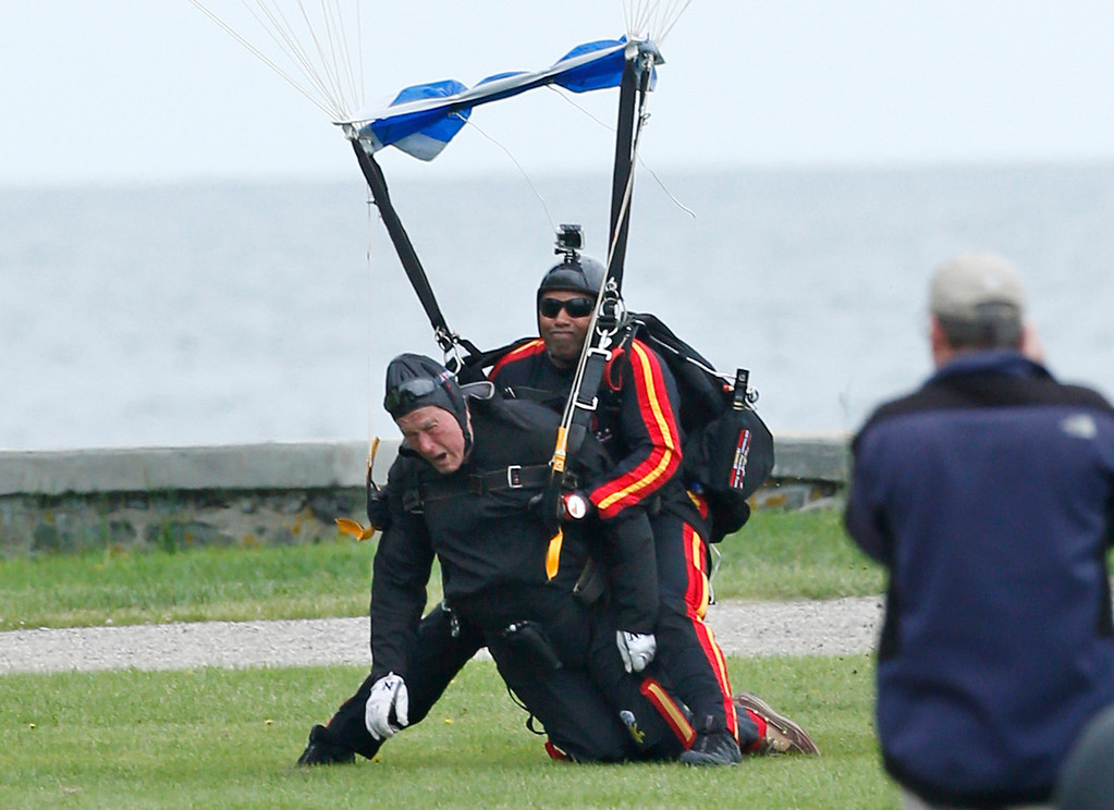 . Former President George H.W. Bush, left, strapped to Sgt. 1st Class Mike Elliott, a retired member of the Army\'s Golden Knights parachute team, land on the lawn at St. Anne\'s Episcopal Church after making a tandem parachute jump near Bush\'s summer home in Kennebunkport, Maine, Thursday, June 12, 2014. Bush made the jump, his eighth, in celebration of his 90th birthday. (AP Photo/Robert F. Bukaty)