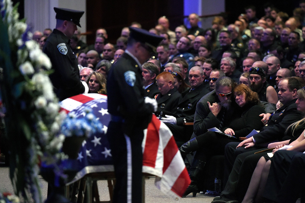""". ARVADA, CO - MARCH 14: John and Melissa Carrigan, the parents of Nate, in glasses and suit middle right, and other family members, right, embrace during the memorial service for Park County Deputy Corporal Nathaniel \""""Nate\"""" Carrigan at Faith Bible Chapel on March 14, 2016 in Arvada, Colorado. Carrigan was killed in the line of duty while serving a warrant in Bailey, Colorado on February 24, 2016. (Photo by Helen H. Richardson/The Denver Post)"""