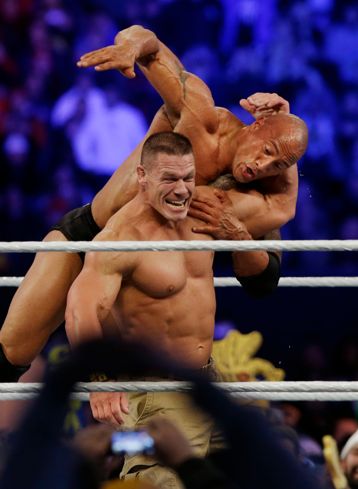 Description of . Wrestler John Cena, left, wrestles with Dwayne Douglas Johnson, known as The Rock  Sunday, April 7, 2013, in East Rutherford, N.J., during Wrestlemania. (AP Photo/Mel Evans)
