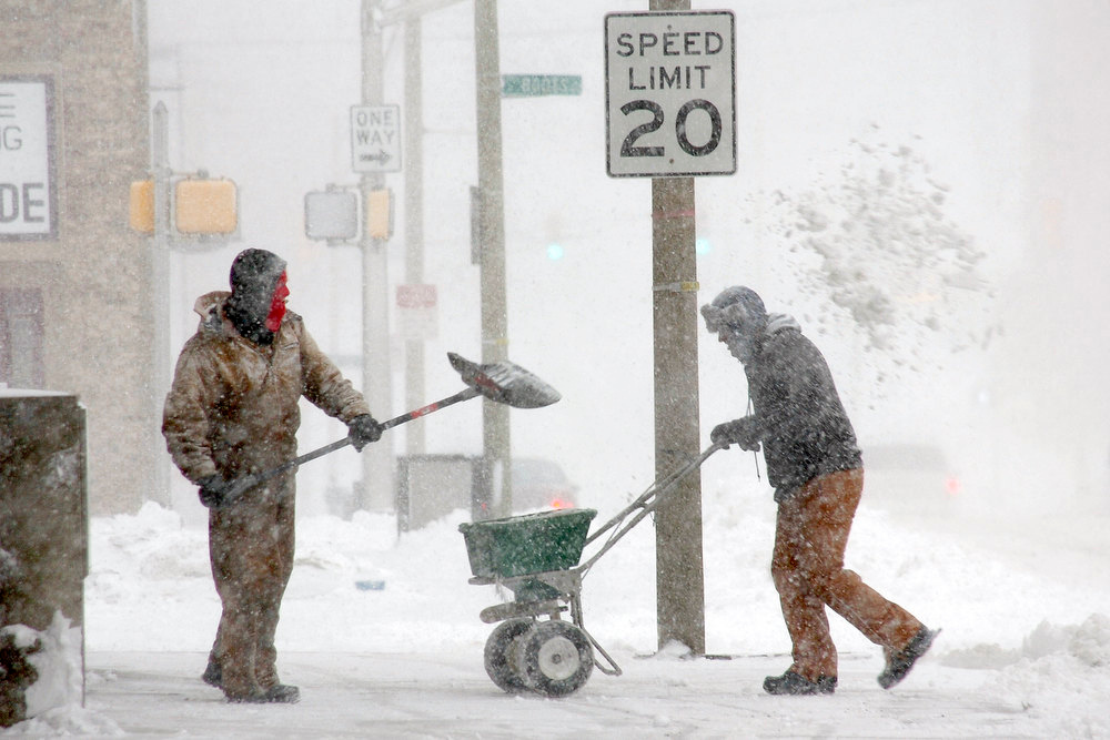 Description of . J & J Lawn Service employees Brock Cowgill, left, and Calvin Parker work to clear the sidewalk in front of Salin Bank in downtown Marion, Ind., on Wednesday, Dec. 26, 2012.  (AP Photo/Chronicle-Tribune, Jeff Morehead)