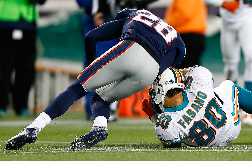 . Anthony Fasano #80 of the Miami Dolphins is hit in the head by Steve Gregory #28 of the New England Patriots during the game at Gillette Stadium on December 30, 2012 in Foxboro, Massachusetts. (Photo by Jared Wickerham/Getty Images)