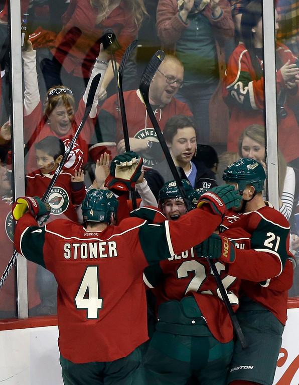 . Minnesota Wild fans celebrate as players swarm around Wild\'s Pierre-Marc Bouchard (center, facing camera) after he scored in the third period of an NHL hockey game against the Colorado Avalanche on Saturday, Jan. 19, 2013, in St. Paul, Minn. The Wild won 4-2. (AP Photo/Jim Mone)