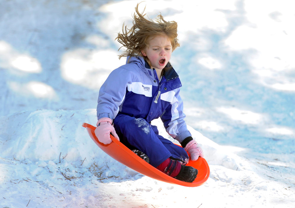 . Faith Budreau, 5, sails off a small jump joining several families gathered at Robinson Park to get in some sledding in before the weekend snow begins to melt later in the week with warmer weather. These Denver families and their kids begin their spring break week today. (Photo By Kathryn Scott Osler/The Denver Post)