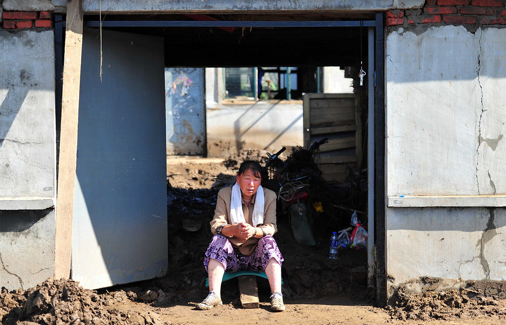 """. A woman sits before her damaged home after floods hit the Qingyuan Manchu autonomous county of Fushun, in northeast China\'s Liaoning province on August 19, 2013. Devastating floods at opposite ends of China have left 105 people dead and another 115 missing in recent days, state media said on August 19. Flooding in the northeast which left 72 people dead was described as \""""the worst in decades\"""" by the state news agency, while another 33 people died in the south as a result of the weather, it said citing the ministry of civil affairs.   AFP PHOTOSTR/AFP/Getty Images"""