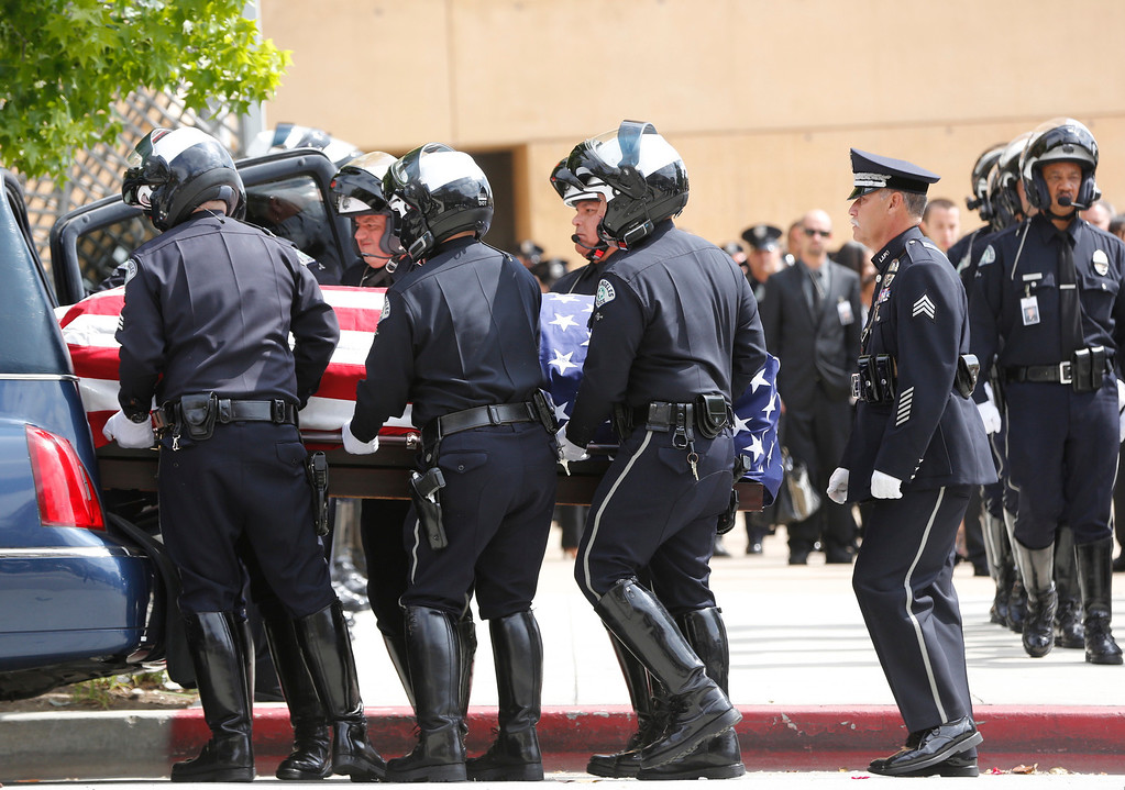 . Pallbearers place the coffin of Los Angeles Police Dept. motorcycle officer Chris Cortijo into a hearse after a funeral service at the Cathedral of Our Lady of the Angels Tuesday morning, April 22, 2014, in Los Angeles. Hundreds of fellow law enforcement officers turned out to mourn 51-year-old officer, who died after he was struck by a motorist allegedly under the influence of cocaine on April 5.(AP Photo/Damian Dovarganes)