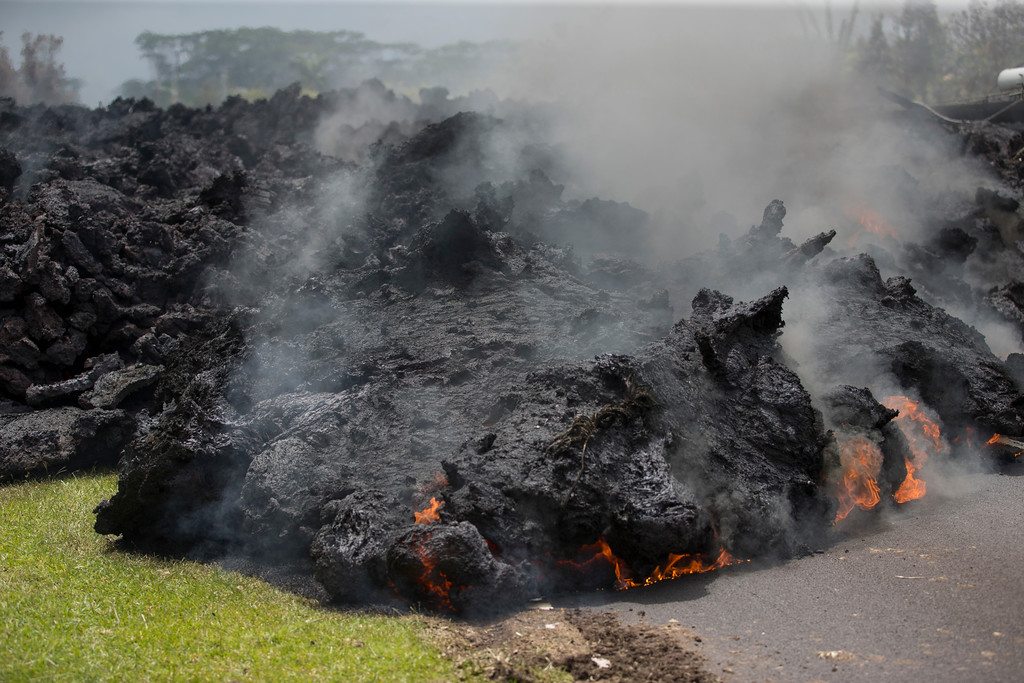 . Lava creeps across the road in the Leilani Estates, Saturday, May 5, 2018, in Pahoa, Hawaii. The Hawaiian Volcanoes Observatory said eight volcanic vents opened in the Big Island residential neighborhood of Leilani Estates since Thursday. The Leilani Estates area is at the greatest risk for more lava outbreaks. (AP Photo/Marco Garcia)
