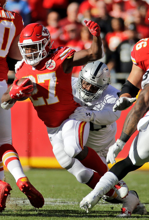 . Kansas City Chiefs running back Kareem Hunt (27) is tackled by Oakland Raiders safety Reggie Nelson (27) during the first half of an NFL football game in Kansas City, Mo., Sunday, Dec. 10, 2017. (AP Photo/Charlie Riedel)