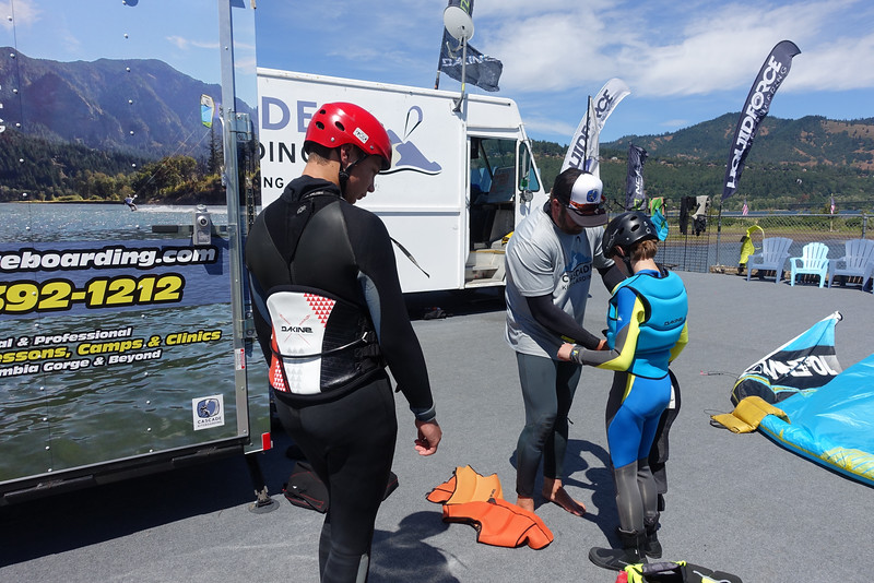 Travis helps Ethan and Brady get ready for their first kiteboarding lesson.
