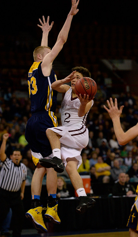 . Alamos Mean Moose Noah Romero (2) flies through the air to take a shot past CS Christian Lions Justin Engesser (33) during the Championship 3A game at the Coliseum. (Photo By John Leyba/The Denver Post)