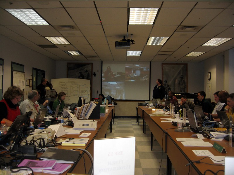 During a status meeting, staff at three other sites give updates via videolink