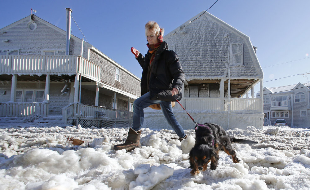 Description of . Marj Bates and her dog Simon walk past houses and a street coated with frozen sea water as they walk down Rebecca Road in Scituate, Mass., Sunday, Feb. 10, 2013.  The coastal town was hit with a storm surge during a fierce winter storm. More than 650,000 homes and businesses were left without electricity. (AP Photo/Charles Krupa)