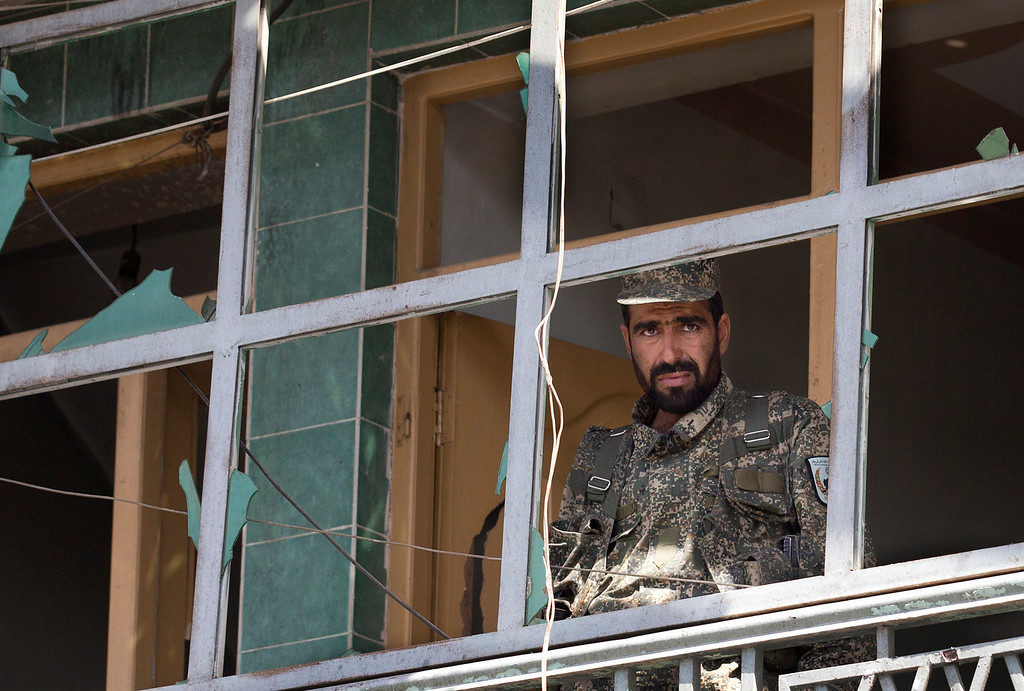 . An Afghan Army soldier peers through a destroyed shop window at the scene where a suicide car bomber attacked a NATO convoy in Kabul, Afghanistan, Thursday, May 16, 2013.  (AP Photo/Anja Niedringhaus)