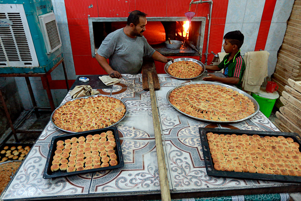 . A baker cooks cookies in preparation for celebrations for the upcoming Muslim Eid al-Fitr to mark the end of the holy fasting month of Ramadan in Baghdad, Iraq, Thursday, June 14, 2018. (AP Photo/Hadi Mizban)