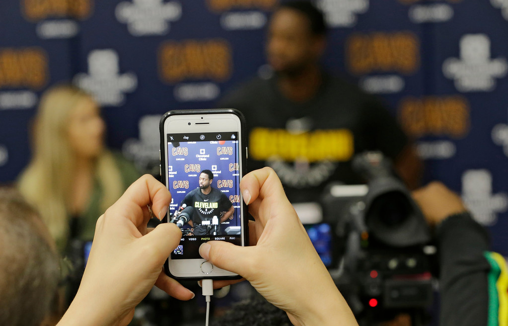 . Cleveland Cavaliers\' Dwyane Wade, displayed on a mobile phone,  answers questions during a news conference at the NBA basketball team\'s training facility, Friday, Sept. 29, 2017, in Independence, Ohio. Wade once convinced LeBron James that Miami was the place to be. Seven years later, James lured Wade to Ohio for the chance to win another NBA title, together.(AP Photo/Tony Dejak)