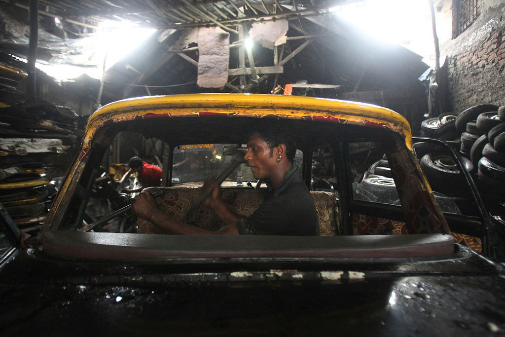 . In this Tuesday, July 30, 2013, an Indian worker dismantles a Mumbai Premier Padmini taxi in a scrapyard in Mumbai, India. More than 400 Premier Padmini taxis are expected to stop running in Mumbai in August in line with a Maharashtra government order that bans cabs that are more than 20 years old running. (AP Photo/Rafiq Maqbool)