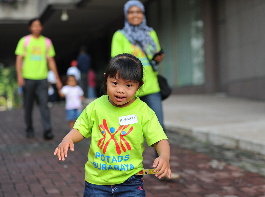 . Indonesian children with Down syndrome walk together as they celebrate World Down Syndrome Day on March 21, 2014 in Surabaya, Indonesia. Today marks the 9th anniversary of World Down Syndrome and focuses on supporting all people with Down syndrome on their right to access healthcare without discrimination and with proper assessment of the specific health needs of the individual.  (Photo by Robertus Pudyanto/Getty Images)