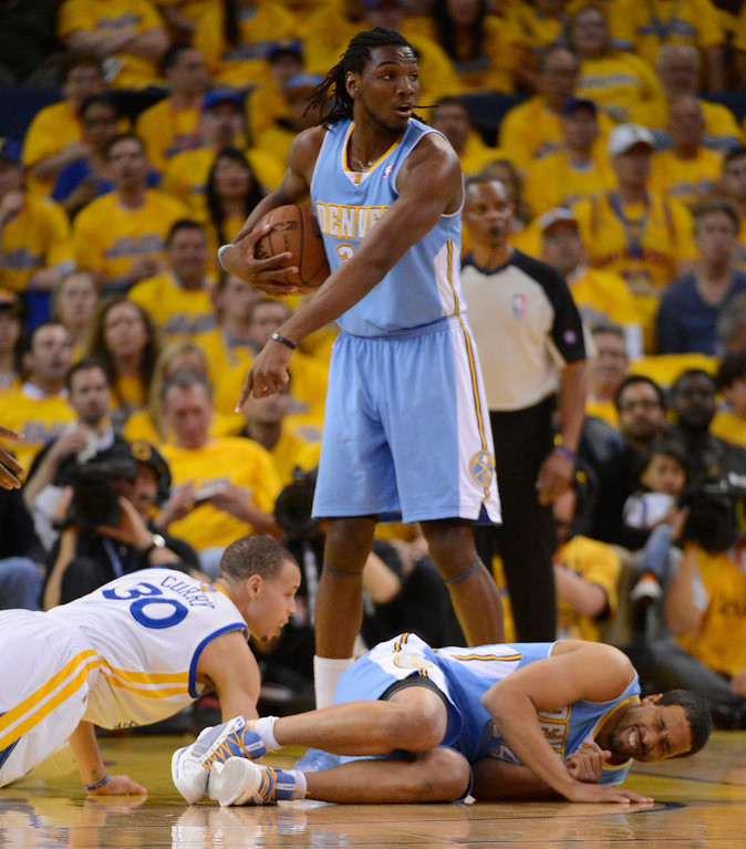 . Andre Miller (24) of the Denver Nuggets and Stephen Curry (30) of the Golden State Warriors lay on the floor after colliding as Kenneth Faried (35) of the Denver Nuggets points at Curry during the second quarter in Game 6 of the first round NBA Playoffs May 2, 2013 at Oracle Arena. Miller was called for the foul (Photo By John Leyba/The Denver Post)