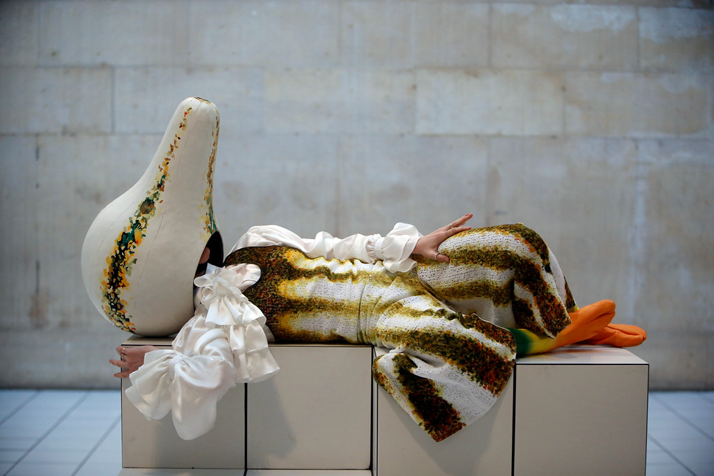 . A performer in a squash-like costume as part of a new work of art by Anthea Hamilton, during a press pre-view at the Tate Britain in London, Wednesday, March 21, 2018. Over 7000 white tiles have been laid in the large galley with selected works from the Tate\'s collection, chosen for their organic form, the tiles formed in to podiums which the performer uses to interact with the work. (AP Photo/Alastair Grant)