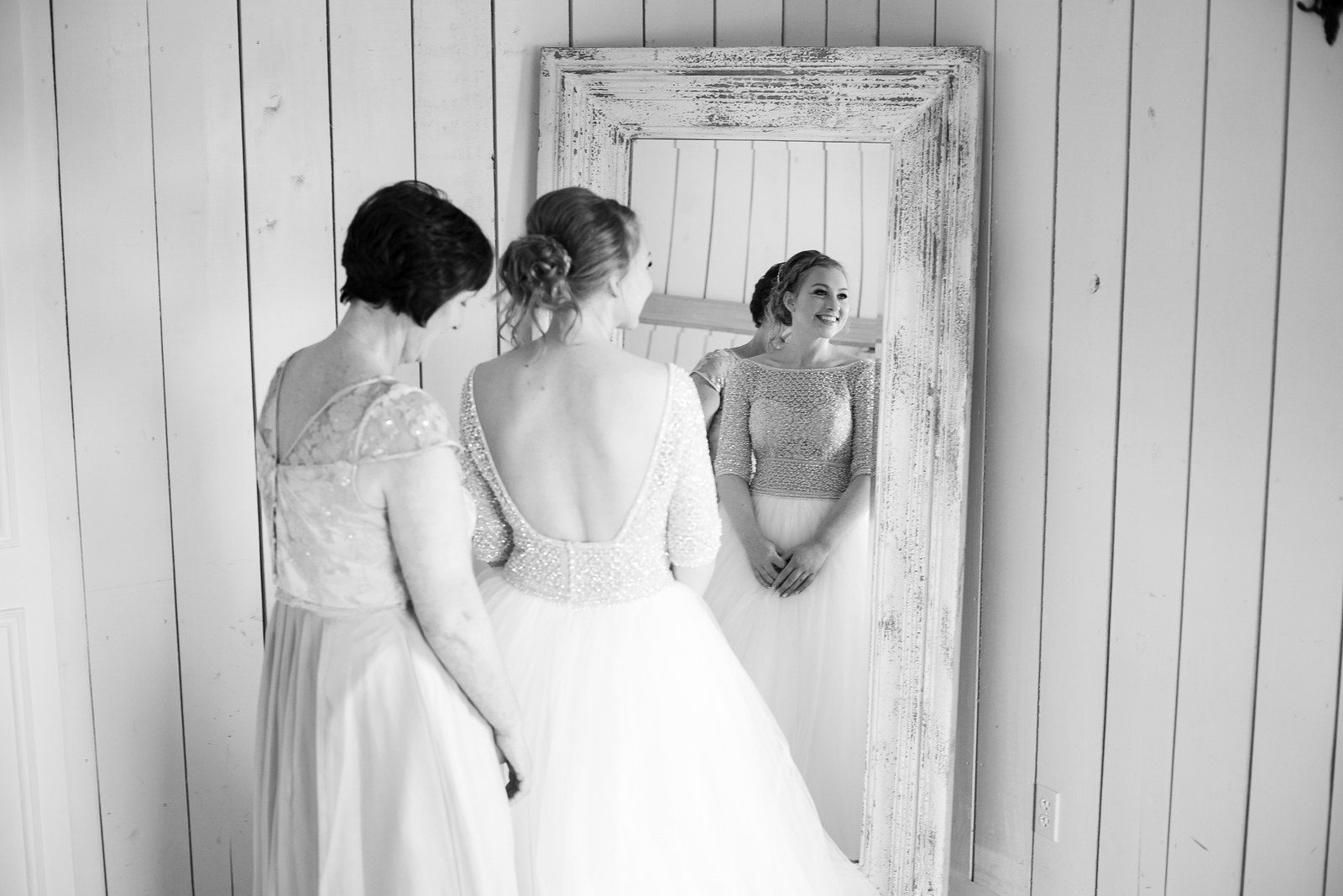 a black and white photo of a bride smiling in the mirror as she gets ready for her wedding