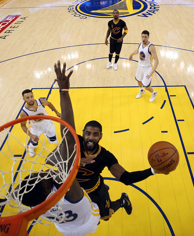 . Cleveland Cavaliers guard Kyrie Irving, center, shoots against Golden State Warriors forward Draymond Green during the second half of Game 5 of basketball\'s NBA Finals in Oakland, Calif., Monday, June 12, 2017. The Warriors won 129-120 to win the NBA championship. (Ezra Shaw/Pool Photo via AP)