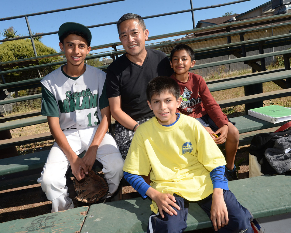 . Dennis Hanley is photographed with Isaac, 13, left, Brian. 11, foreground, and Chris, 10, right,  three boys adopted through the Adopt a Special Kid Agency, just before Isaac\'s baseball game at Bushrod Field in Oakland, Calif., on Thursday, June 20, 2013.  (Dan Honda/Bay Area News Group)