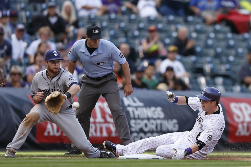 . Corey Dickerson #6 of the Colorado Rockies slides at third base ahead of the throw to Cory Spangenberg #15 of the San Diego Padres in the seventh inning of the game at Coors Field on September 7, 2014 in Denver, Colorado. The Rockies won 6-0. (Photo by Joe Robbins/Getty Images)