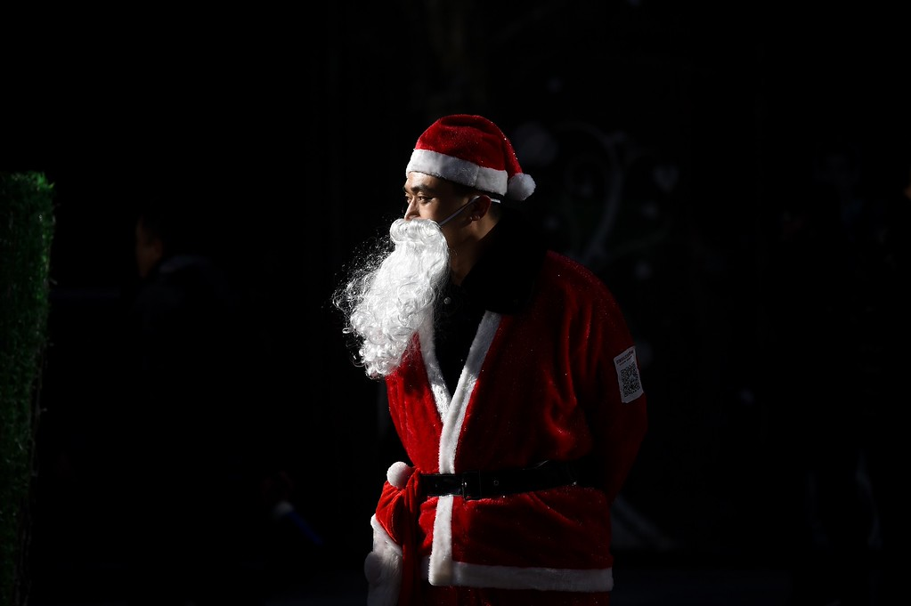 . A salesman dressed as Santa Claus waits for customers at the entrance of a shop in Beijing on December 25, 2014. Christmas -- once banned in China -- has exploded in the atheist nation in recent years, with marketers using everything from saxophones and smurfs to steam trains to get shoppers to open their wallets. WANG ZHAO/AFP/Getty Images