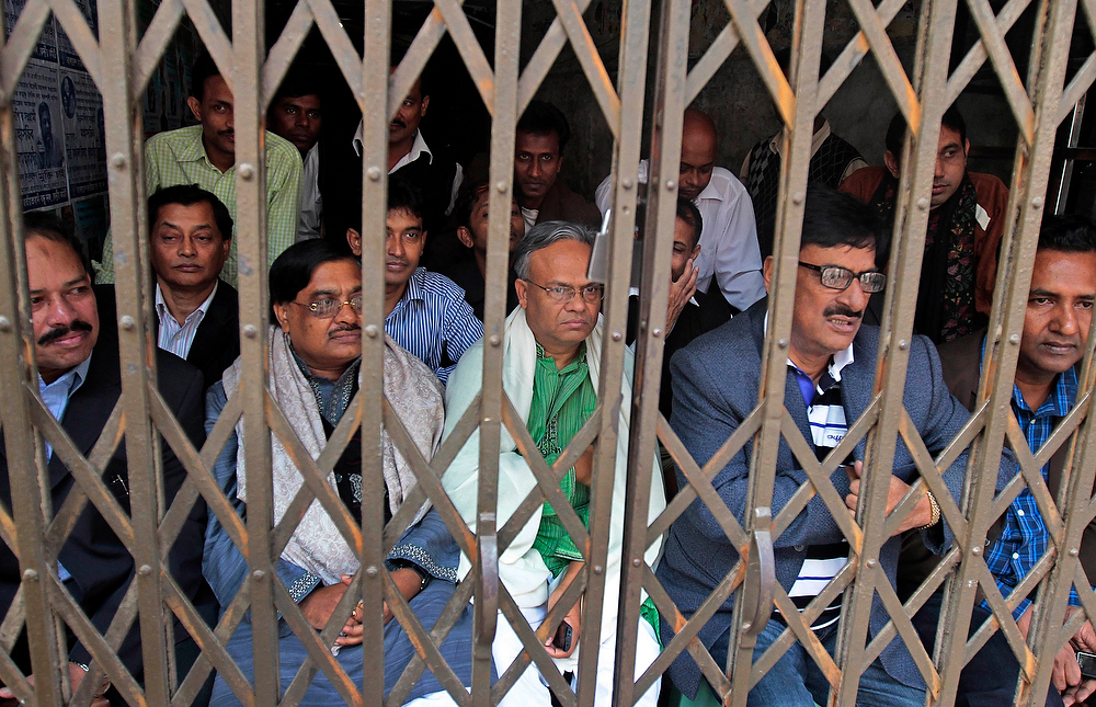 Description of . Bangladesh's opposition Nationalist Party activists sit at the entrance of their office as they are prevented from stepping out by police during a nationwide half-day strike in Dhaka, Bangladesh, on Thursday, Dec. 13, 2012. A coalition of 18 opposition parties was enforcing the strike to demand that the caretaker government be restored before the next national elections due in 2014. A key coalition partner is also pressing for freedom of its leaders facing charges of crimes against humanity involving 1971 independence war against Pakistan. The protest is led by Bangladesh Nationalist Party. (AP Photo/A.M. Ahad)