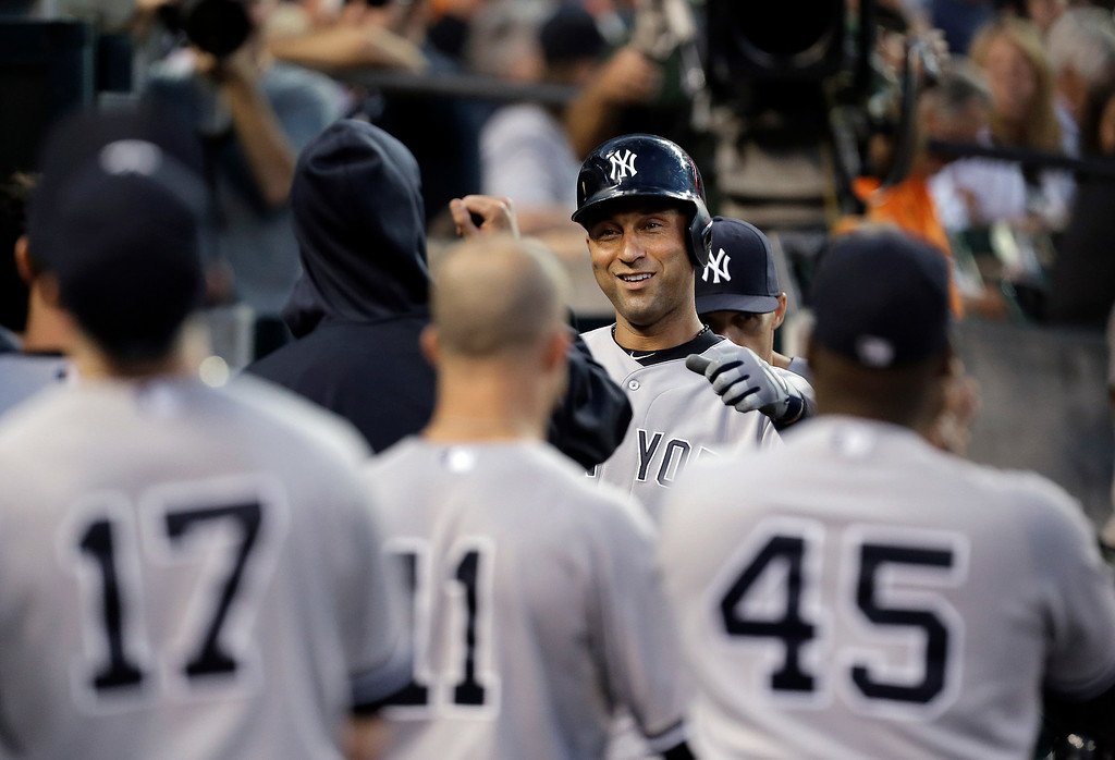 . New York Yankees\' Derek Jeter celebrates after scoring on a Mark Teixeira double against the Detroit Tigers in the third inning of a baseball game in Detroit, Wednesday, Aug. 27, 2014. (AP Photo/Paul Sancya)