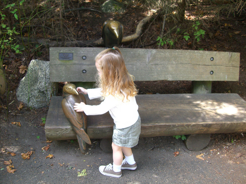 Petting a fake bird on a bench.