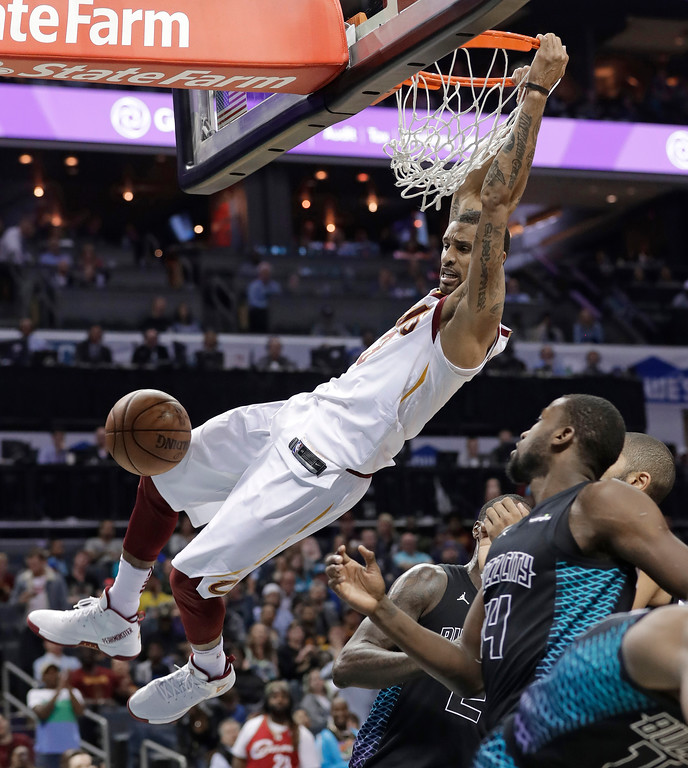 . Cleveland Cavaliers\' George Hill dunks past Charlotte Hornets\' Michael Kidd-Gilchrist, right, during the second half of an NBA basketball game in Charlotte, N.C., Wednesday, March 28, 2018. (AP Photo/Chuck Burton)