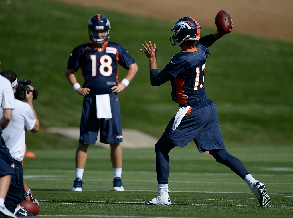 . Denver Broncos quarterback Brock Osweiler (17) throws a pass as Denver Broncos quarterback Peyton Manning (18) looks on during drills during the first day of the Denver Broncos 2014 training camp July 24, 2014 at Dove Valley. (Photo by John Leyba/The Denver Post)