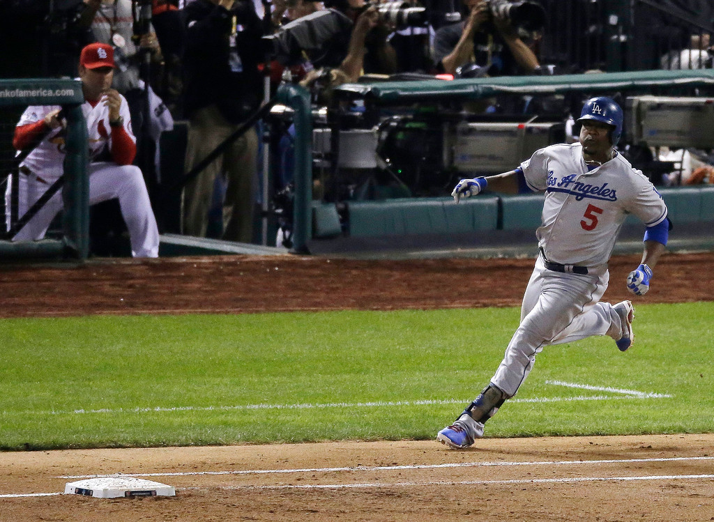 . Los Angeles Dodgers\' Juan Uribe runs after hitting a two-run scoring single during the third inning of Game 1 of the National League baseball championship series against the St. Louis Cardinals, Friday, Oct. 11, 2013, in St. Louis. (AP Photo/Chris Carlson)