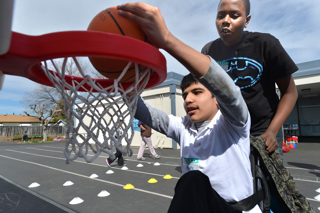 . Makoully, 14, of Oakley, an eighth grader at Park Middle School, tries to dunk the basketball as his classmate Ja\'Sahn, 11, of Antioch looks on during a Special Olympics basketball skills event at Turner Elementary School in Antioch, Calif., on Friday March 8, 2013.  (Dan Rosenstrauch/Staff)