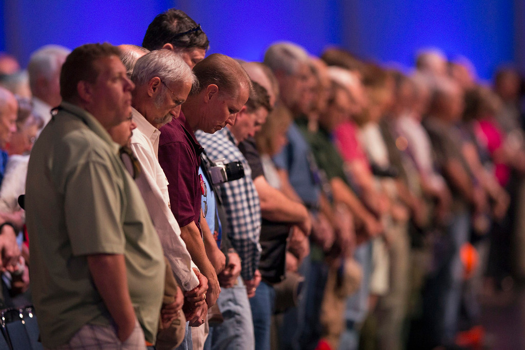 . National Rifle Association members bow their heads in prayer before the start of the Annual Meeting of Members in Houston, Texas on May 4, 2013. Organizers expect some 70,000 attendees at the 142nd NRA Annual Meetings & Exhibits in Houston, which began on Friday and continues through Sunday. REUTERS/Adrees Latif