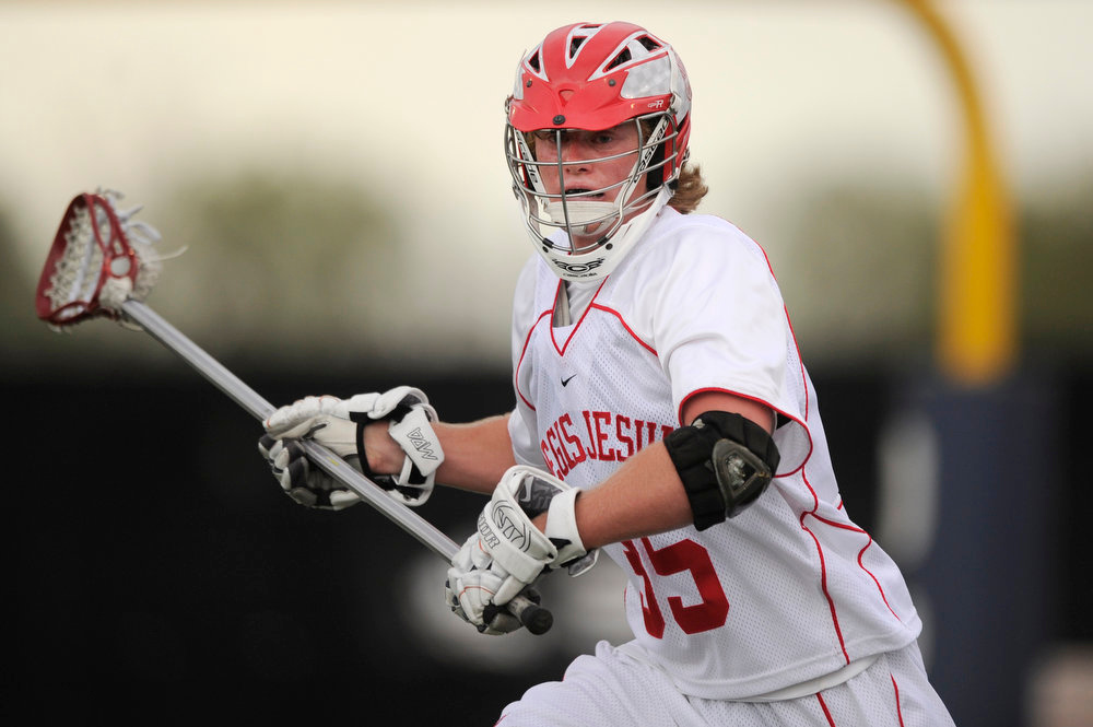 . Regis Jesuit defenseman Ian Demond #15 carries the ball against Arapahoe High School during a CHSAA 5A boys lacrosse semifinal on May 15, 2013, in Denver, Colorado. Arapahoe won 13-5 to advance to the finals. (Photo by Daniel Petty/The Denver Post)
