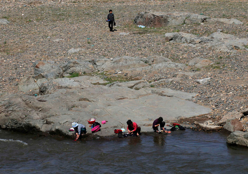 . People wash clothes on the banks of a river near the North Korean city of Hyesan, across the Yalu River from the Chinese town of Changbai May 12, 2013. Chinese currency and U.S. dollars are being used more widely than ever in North Korea instead of the country\'s own money. The use of dollars and Chinese yuan, or renminbi, has accelerated since a revaluation of the North Korean won in 2009 wiped out the savings of millions of people, said experts on the country, defectors and Chinese border traders.  REUTERS/John Ruwitch