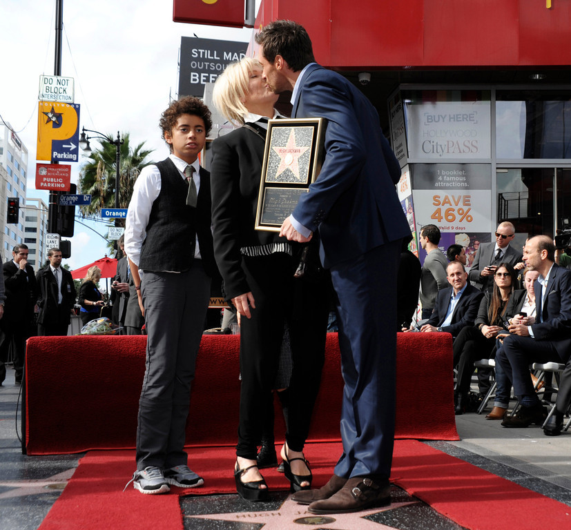 . Actor Hugh Jackman, right, and his wife, actress Deborra-Lee Furness, share a kiss, while their son, Oscar Jackman, looks on at Hugh Jackman\'s star ceremony at the Hollywood Walk of Fame on Thursday, Dec. 13, 2012, in Los Angeles. (Photo by Dan Steinberg/Invision/AP)