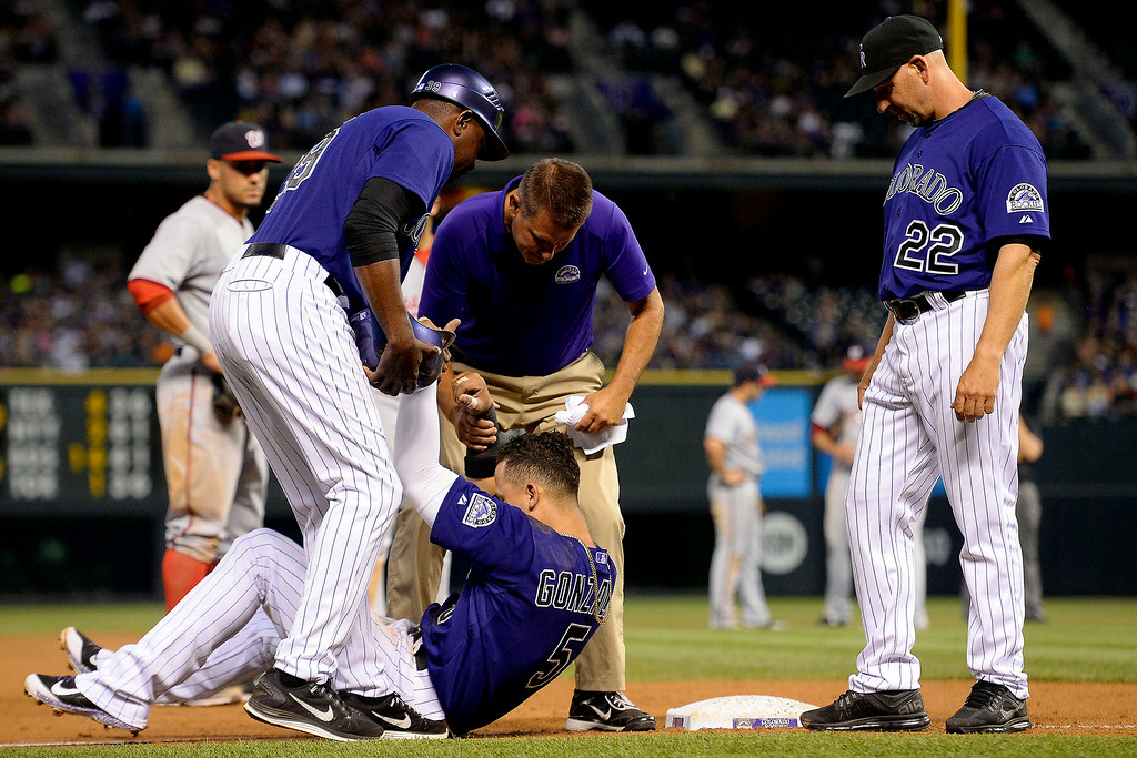 . Carlos Gonzalez (5) of the Colorado Rockies lays at third base as manager Walt Weiss (22) and Stu Cole (39) look over him after he failed to make a clean slide safely while hurting himself in the process at Coors Field. Major League Baseball action between the Colorado Rockies and the Washington Nationals on Monday, July 21, 2014. (Photo by AAron Ontiveroz/The Denver Post)