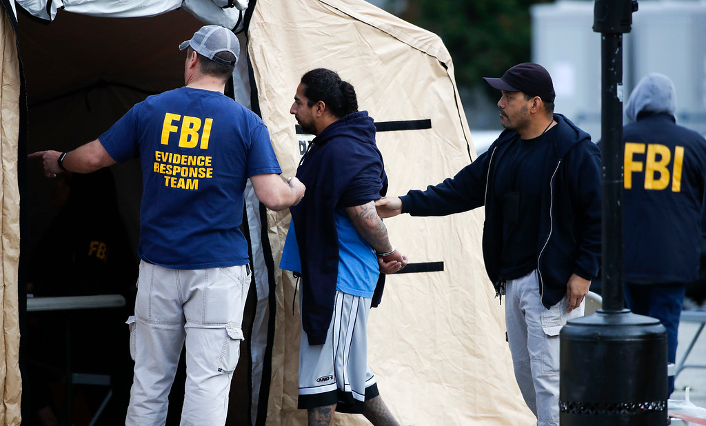 . A man is taken into custody by FBI agents Wednesday, May 17, 2017, in Los Angeles. Hundreds of federal and local law enforcement fanned out across Los Angeles, serving arrest and search warrants as part of a three-year investigation into the violent and brutal street gang MS-13. (AP Photo/Jae C. Hong)