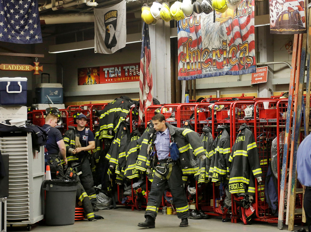 . A firefighter with Engine 10 Company 10 puts on his gear as a call comes into his firehouse adjacent to the World Trade Center, Thursday, Sept. 11, 2014 in New York. Three hundred forty three New York firefighters were killed in the terrorist attacks of Sept. 11, 2001. (AP Photo/Mark Lennihan)