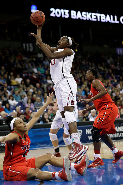 . Stanford\'s Chiney Ogwumike, center, shoot and scores as Georgia\'s Jasmine Hassell, left, falls to the floor and Krista Donald watches in the first half of a regional semifinal game in the NCAA women\'s college basketball tournament Saturday, March 30, 2013, in Spokane, Wash. (AP Photo/Elaine Thompson)
