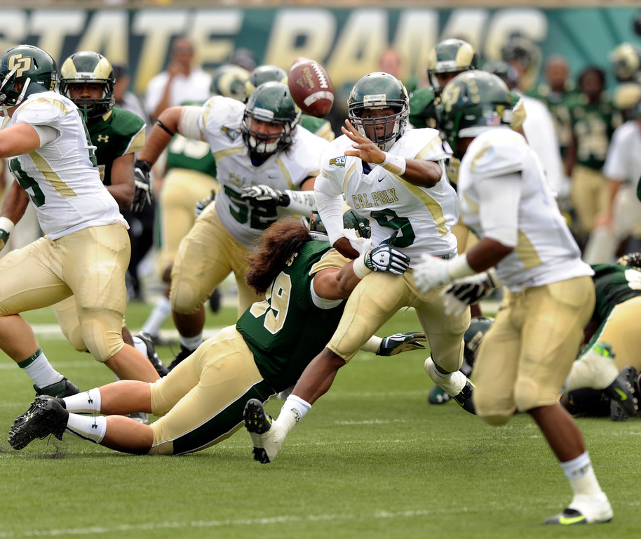 . FORT COLLINS, CO. - SEPTEMBER 14: Rams\' defensive end Eli Edwards (99) hit Cal Poly quarterback Chris Brown (9) as he pitched to Kristaan Ivory in the first half. The Colorado State University football team hosted Cal Poly at Hughes Stadium in Fort Collins Saturday afternoon, September 14, 2013.  Photo By Karl Gehring/The Denver Post