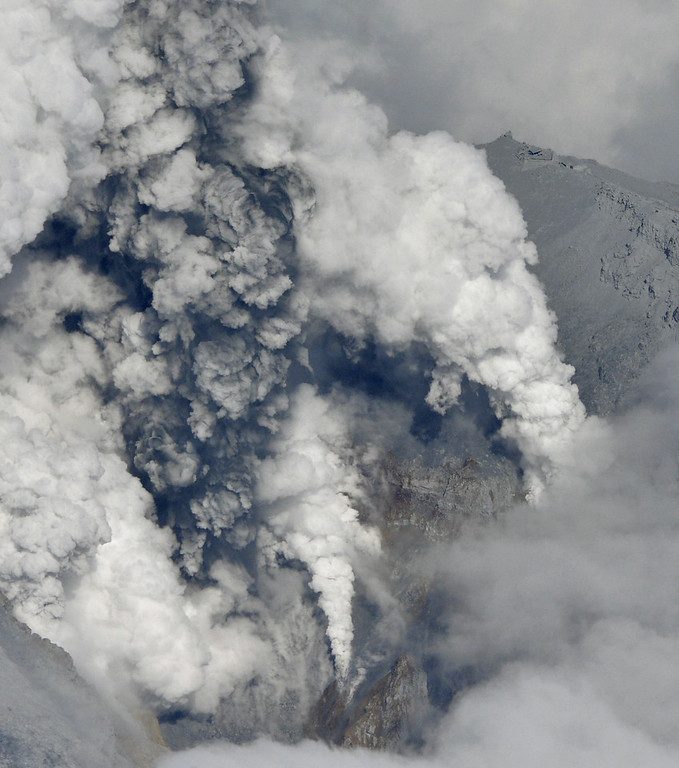 . Dense plumes are spewed out from the crater of Mt. Ontake as the volcano erupts in central Japan Saturday, Sept. 27, 2014. With a sound likened to thunder, the 3,067-meter (10,062-foot) mountain spewed large white plumes high into the sky, sending people fleeing and covering surrounding areas in ash. Buildings of a mountain lodge are seen at top right. (AP Photo/Kyodo News)