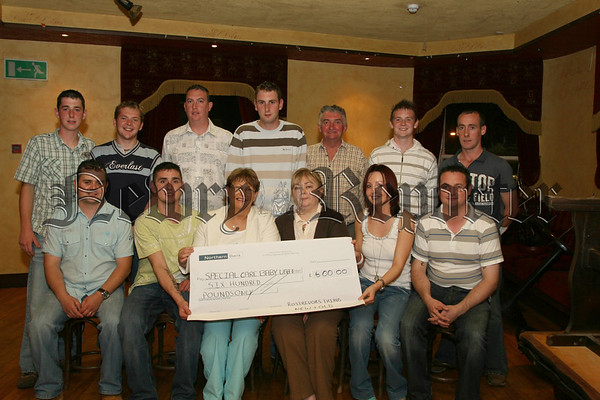 A Charity Gaelic Foorball match between Rostrevor 3rds of yesterday and the present 3rds team took place during the Fiddlersgreen Festival,  A total of £600.00 was raised and the money went to the Special Care Baby Unit in Daisyhill Hospital, Players from both teams are pictured presenting the cheque to Sister Judy Grant and Staff Mid-Wife Nurse Crossan (seated centre). 07W35N58
