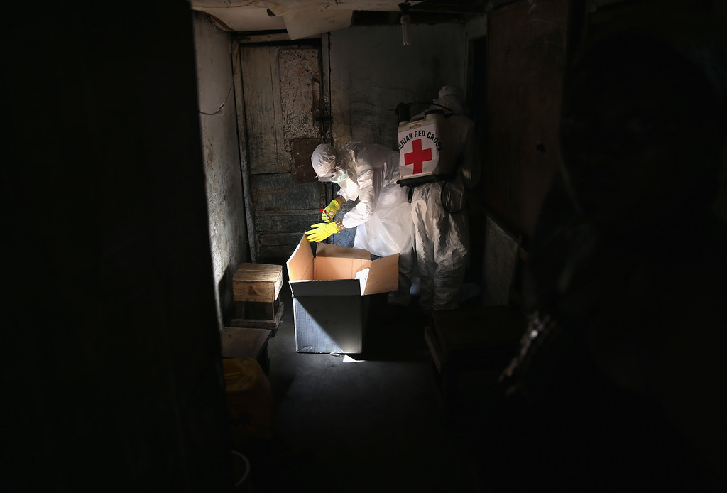 ". A Liberian Red Cross burial team prepares to test the body of a toddler for Ebola while collecting it from a home in the West Point township on January 28, 2015 in Monrovia, Liberia. They were to deliver the body to a new ""safe burial\"" cemetery, operated by USAID-funded Global Communities, where almost 300 people have been interred in its first month of operation. Increasingly fewer of the bodies have come from Ebola Treatment Units (ETUs), as infection rates decline. The cemetery, where burial team members wear protective clothing, (PPE), has been seen in Monrovia as a major achievement, as families of the deceased are permitted to view the burials, important in Liberian culture. In an effort to control the Ebola epidemic in 2014, the Liberian government had ordered the cremation of all deceased in the capital, often further traumatizing surviving family members and unintentionally encouraging many families to hide their dead for secret burials.  (Photo by John Moore/Getty Images)"