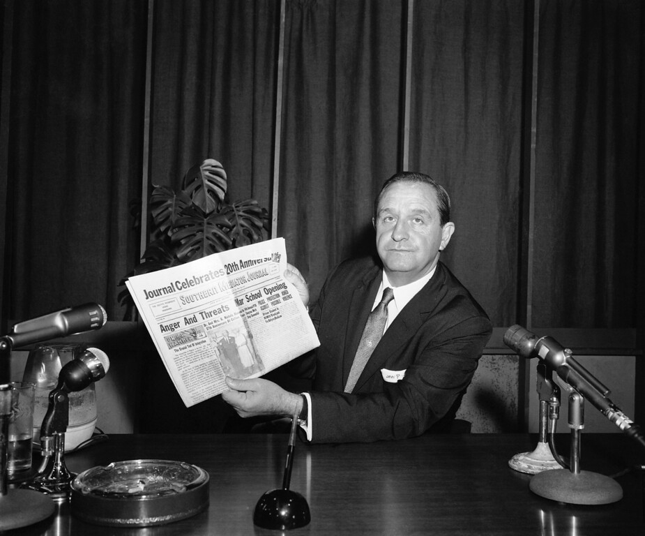 """. Gov. Orval Faubus shows his television audience a local black newspaper headline: \""""Anger and Threats Mar School Opening\"""" in Little Rock, Sept. 3, 1957. He then directed the National Guard to maintain \""""peace and order\"""" at Central High School where racial integration was scheduled. (AP Photo)"""