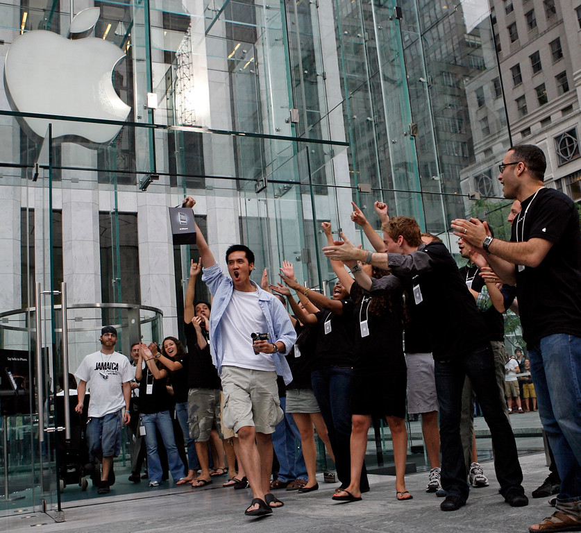 . Apple employees cheers as an excited customer leaves the Apple Store with his new iPhone Friday, June 29, 2007 in New York.  (AP Photo/Jason DeCrow)